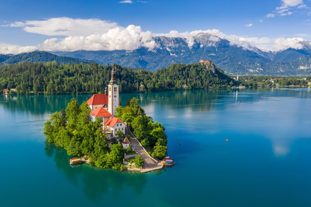 Bled island on Lake Bled with Bled Castle and mountains in the background