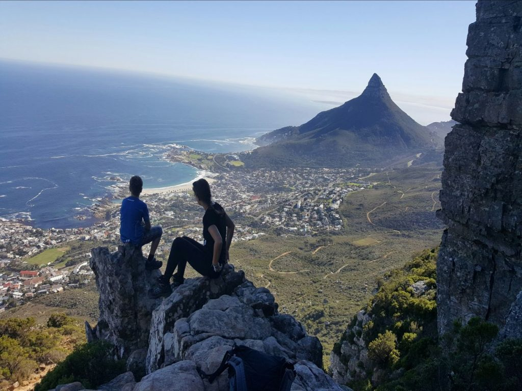 Two hikers sit on a rock on the Table Mountain and watch the ocean