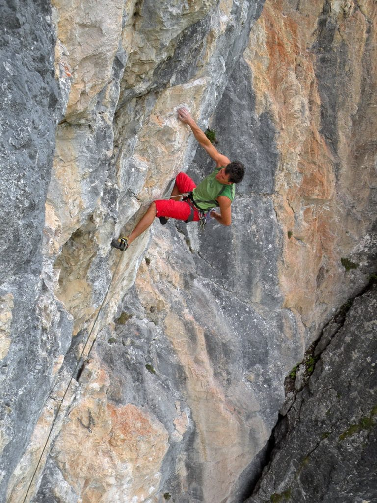 Climber on the rock wall in Dolomites