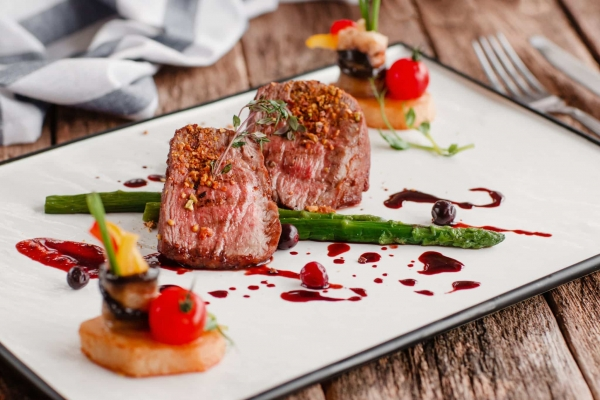 Nice meat dish on a white plate with decoration