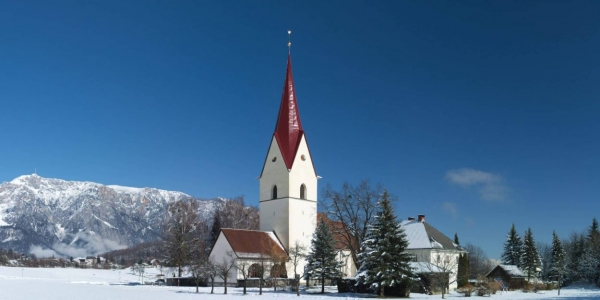 Winter view of the church with snow and the Alps in the background, Arnoldstein