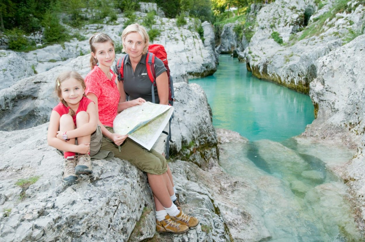 Family sitting by Soča River