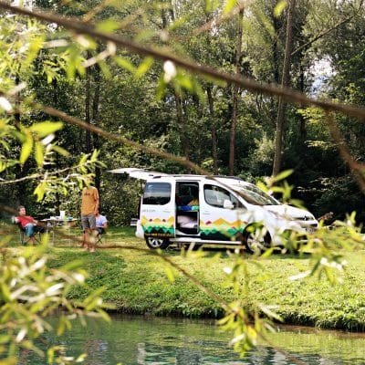 Small campervan camping by the river