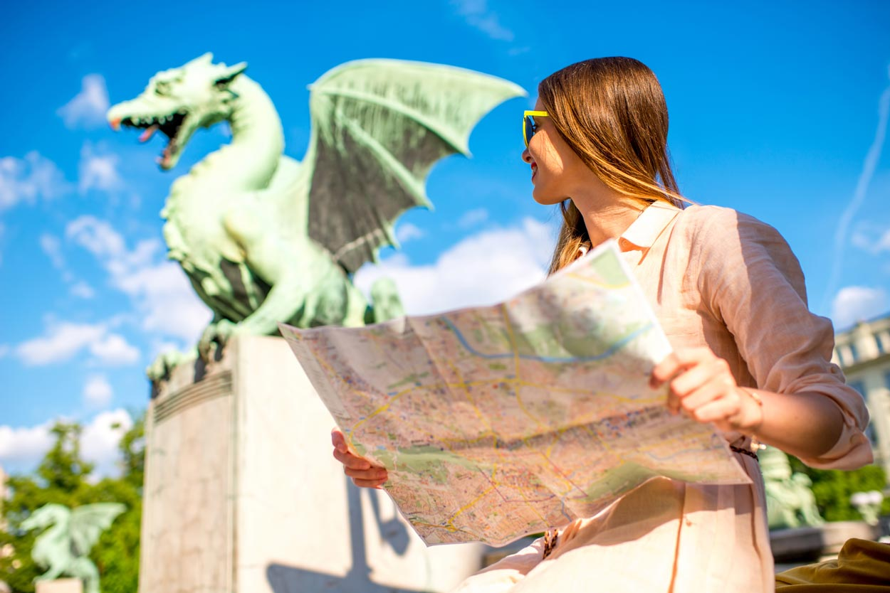 Girl holding a map next to Dragon Bridge in Ljubljana